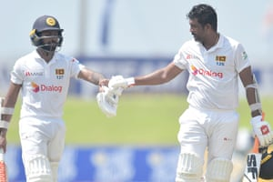 Niroshan Dickwella (left) and Dilruwan Perera bump his fists as they walk off to the lunch.