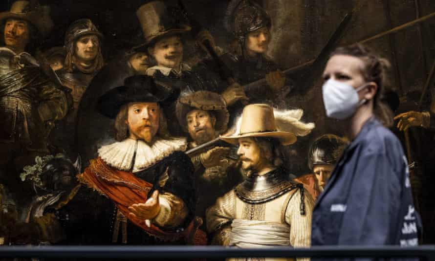 a rijksmuseum worker prepares the restored night watch for public display