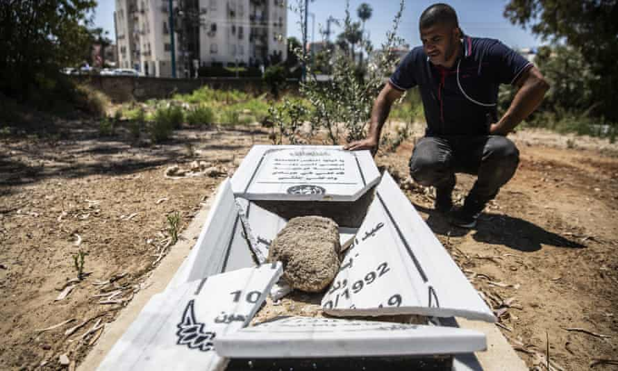 Jamal Abu Kasher, a resident of Lod, looks at one of the several vandalised graves in a Muslim cemetery in Lod, Israel.