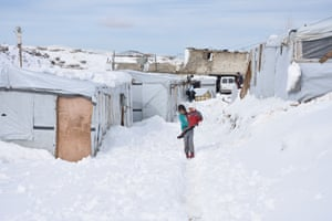 A girl carries a baby as she walks through in snow at a refugee camp in Arsal, Lebanon. The living conditions became harsher in the Arsal refugee camp housing about sixty thousands Syrians, as a result of decrease of aid reaching to the region in recent years and hard winter weather.