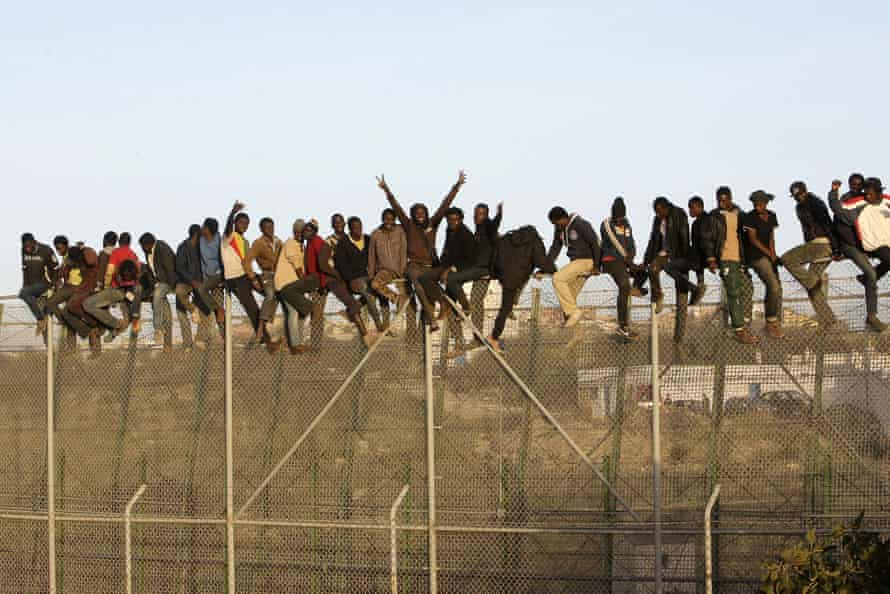 Migrants sit on top of a fence as they attempt to reach Melilla, the Spanish enclave on the north African coast, in October 2014.