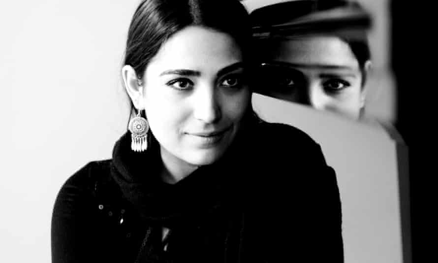 A black and white portrait of Varduhi Yeritsyan sits next to a highly polished upright piano, her gaze off camera, the reflection in the piano looks directly at the viewer