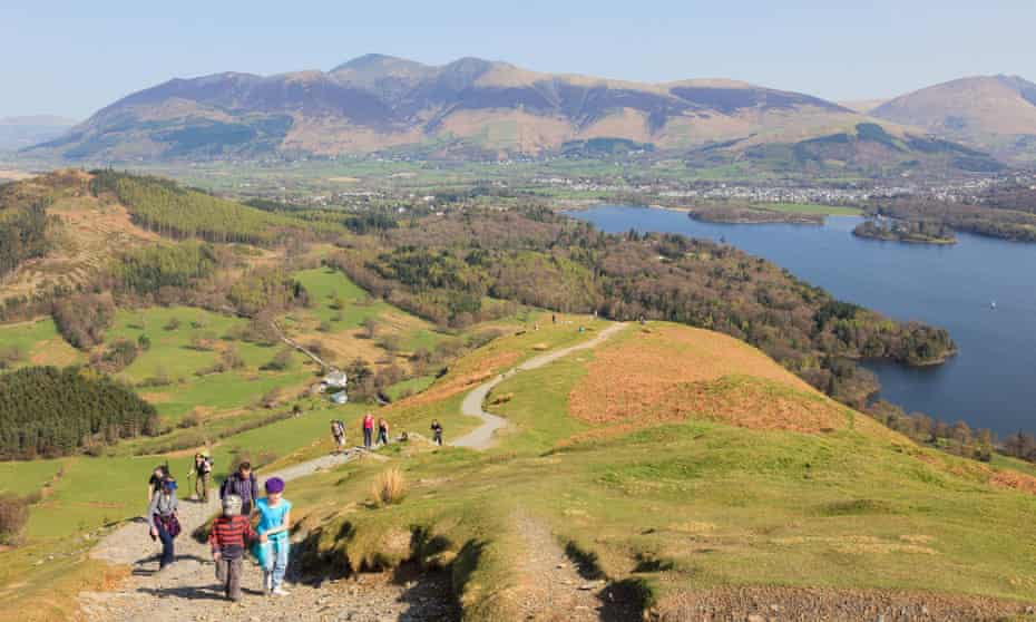 Families walking up Catbells on sunny day with view overlooking Derwent Water