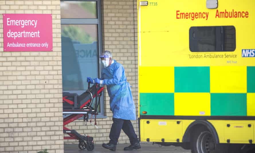 An NHS worker wheels a trolley from an ambulance