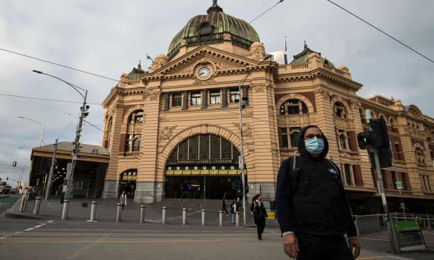 Masked man outside Flinders Street station