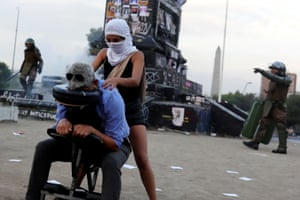 Santiago, Chile. A demonstrator gives a massage during an anti-government protest at Plaza Italia