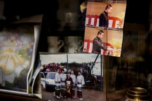 Pictures of Takashi's family and his junior high school graduation on display in his foster home.