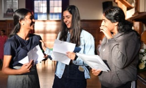 A-Level students (from left) Krishika Balakrishnan, who received two A*s and two As; Ayeesha Sohail, who achieved three A*s and a B; and Daveena Malhi (no details) celebrate their results at King Edward VI high school for girls in Birmingham.