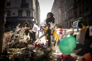 A woman cries as she stands at a makeshift memorial to the victims of the Paris attacks in front of La Casa Nostra restaurant