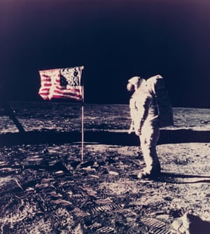 Aldrin stands next to the American flag, mounted on a plastic tube. Cables, lower left, lead to the TV camera