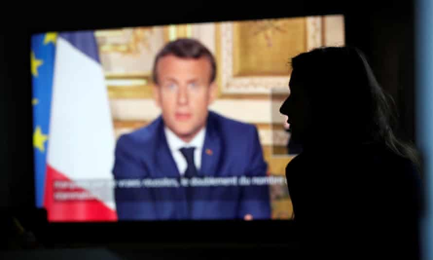 A woman watches as the French president, Emmanuel Macron, addresses the nation.