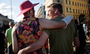 Two participants in the alternative CSD parade walk arm in arm through Berlin's Kreuzberg district, Germany
