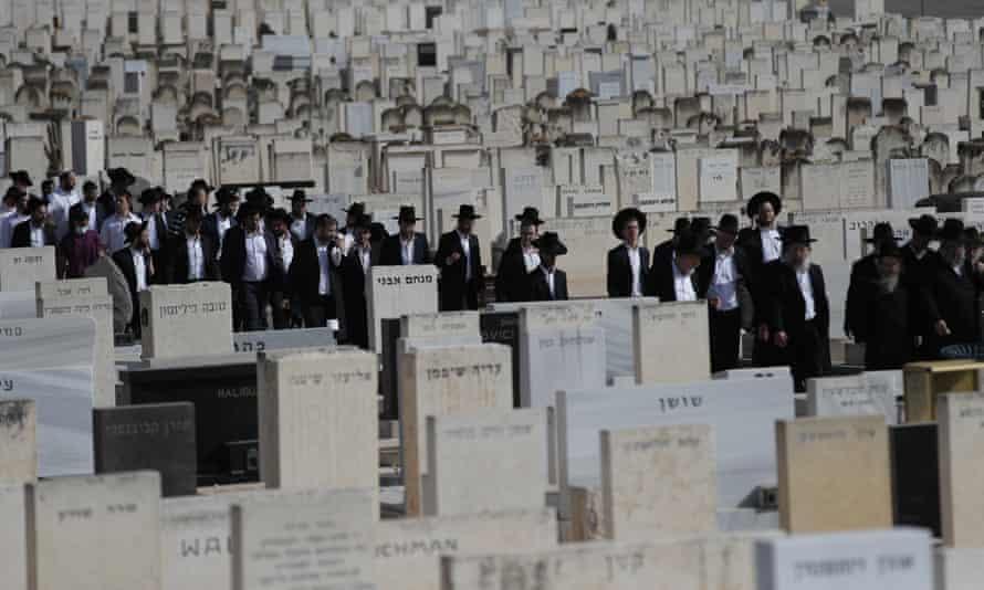 Os enlutados caminham por um cemitério para o funeral de Menahem Zachach, 24, em Petah Tikva, a leste de Tel Aviv.