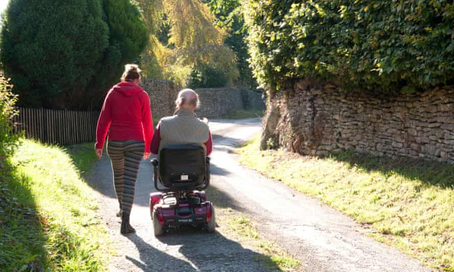 Man using a mobility scooter with his carer walking beside