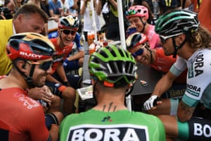 Toulouse, France Peter Sagan, wearing the best sprinter's green jersey, Daniel Oss (right) and other cyclists react as a magician performs a card trick before the start of the twelfth stage of the Tour de France