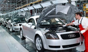 A worker checks the engine compartment of an Audi TT Coupe at the Audi factory in Gyoer, Hungary.