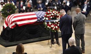 The Senate minority leader, Chuck Schumer, and the South Carolina senator Tim Scott place a wreath at the casket of the late congressman John Lewis.