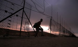 A Palestinian illegally crosses the Israeli security fence through a hole, entering Israel from the outskirts of Hebron