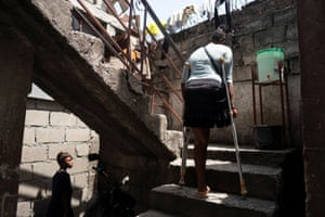 A woman climbs the stairs at a school where people with disabilities and their families have been taking shelter after their settlement was burned down by gangs a month ago, in Port-au-Prince, Haiti. Officials say thousands of people have lost their homes to violent gangs moving into central and southern parts of the city.