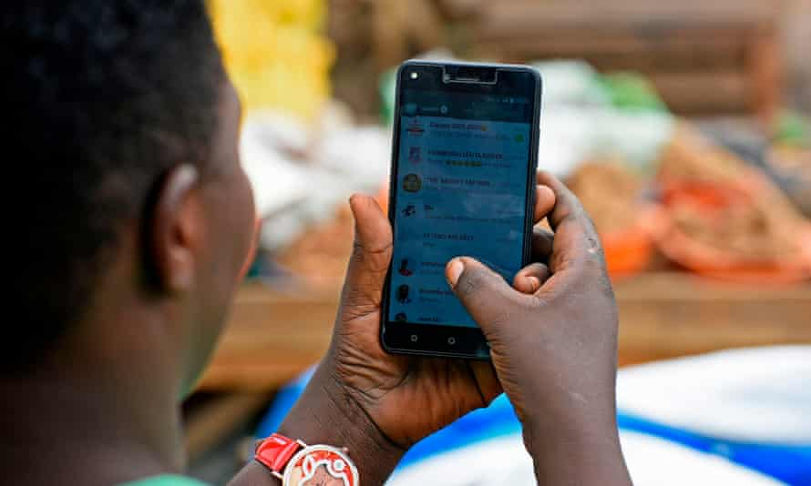 A woman in Kampala scrolls through her WhatsApp messages