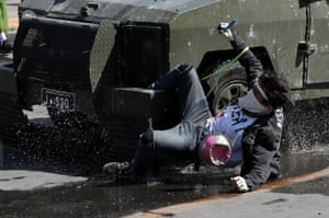 A demonstrator is run over by a riot police vehicle