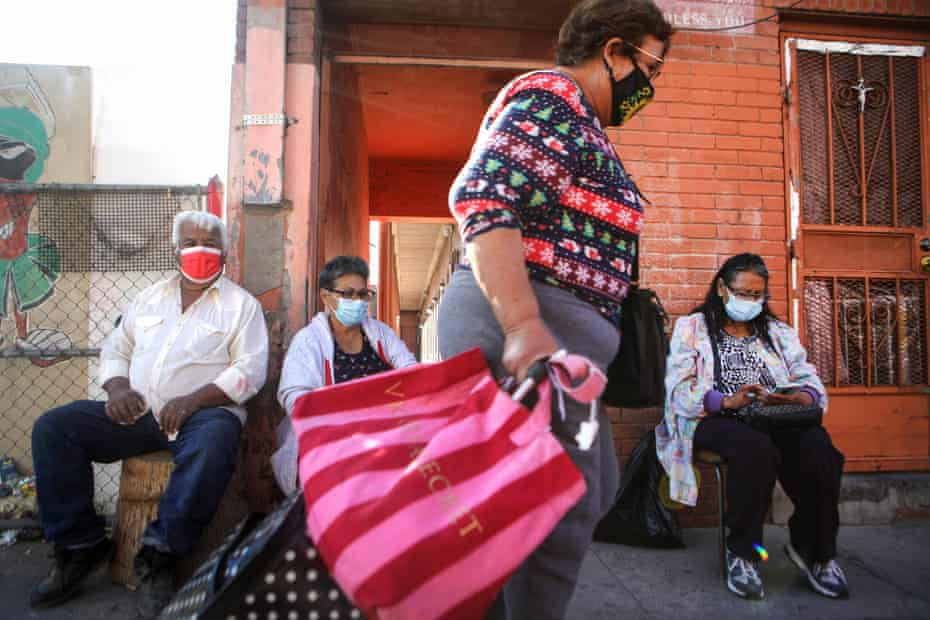 Residents wear face masks as they sit on a sidewalk in El Paso as a woman walks past on 18 November.