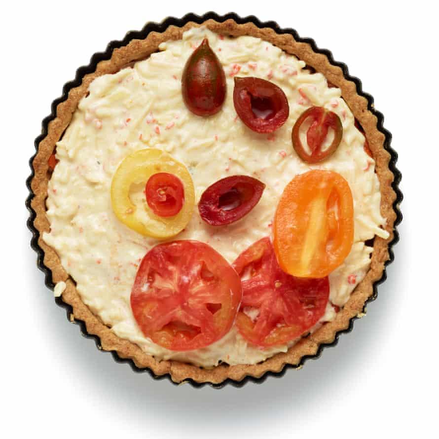 Para armar el pastel, esparza el queso restante sobre la base, luego mezcla los tomates pera horneados con la mezcla de cebolla y colócalos encima.  Unte encima la mezcla de mayonesa y luego termine con los tomates escurridos.