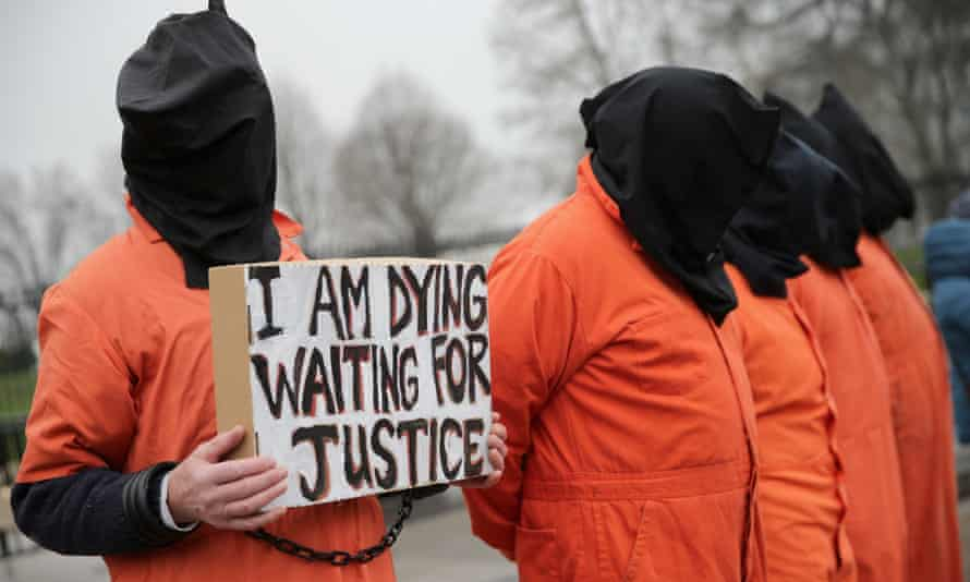 Demonstrators with the group Witness Against Torture dress in orange jumpsuits and wear black hoods while demanding that U.S. President Barack Obama close the military prison in Guantánamo, Cuba, on 8 January.
