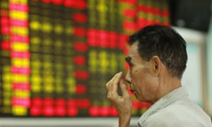 man in front of board of blurred share prices