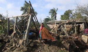 A woman cleans her house damaged by Cyclone Bulbul in Bakkhali, West Bengal