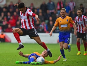 Danny Rose slides in on Josh Ginnelly as Mansfield ended Lincoln's bid to go a year unbeaten at 364 days with a 1-0 win at Sincil Bank