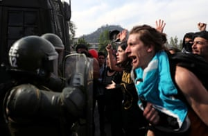 Demonstrators shout at soldiers in Santiago