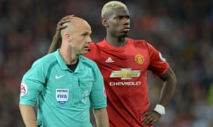 The referee Anthony Taylor with Paul Pogba of Manchester United