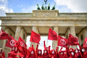 Red Rebel Brigade activists holding up arms and Extinction Rebellion flags in front of the Brandenburg Gate