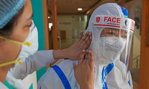 A colleague helps a nurse put on PPE in Max hospital, New Delhi.