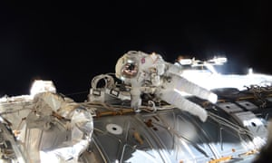 Two astronauts in black space outside the ISS.