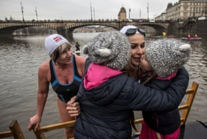 Girls kiss a swimmer as she climbs out of the Vltava river in Prague