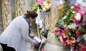 A woman reads a note attached to flowers outside a mosque