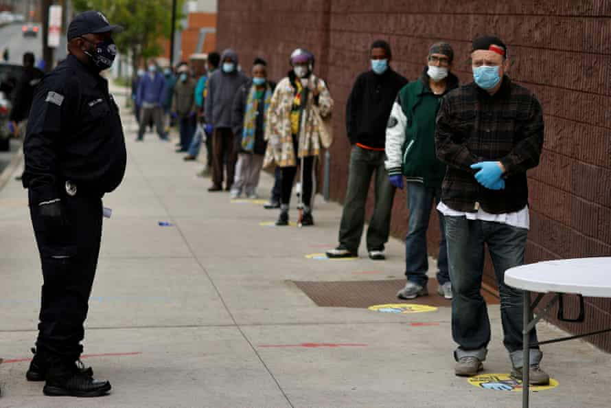 People stand in line to receive bags containing meals, face masks and other personal protective supplies for residents in need outside the NAN Newark Tech World during the outbreak of the coronavirus disease in Newark, New Jersey, U.S.