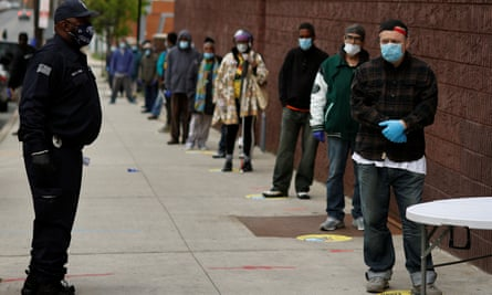 People stand in line to receive bags containing meals, face masks and other personal protective supplies for residents in need in Newark, New Jersey.