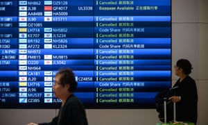 Travellers walk past an arrival board showing cancelled flights at Haneda airport in Tokyo.