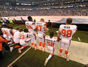 Cleveland Browns players stand and kneel according to choice, during the anthem before their game against the Indianapolis Colts at Lucas Oil Stadium.