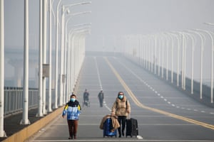 A mother and her son arrive from Hubei province at a checkpoint at the Jiujiang Yangtze River Bridge in January.