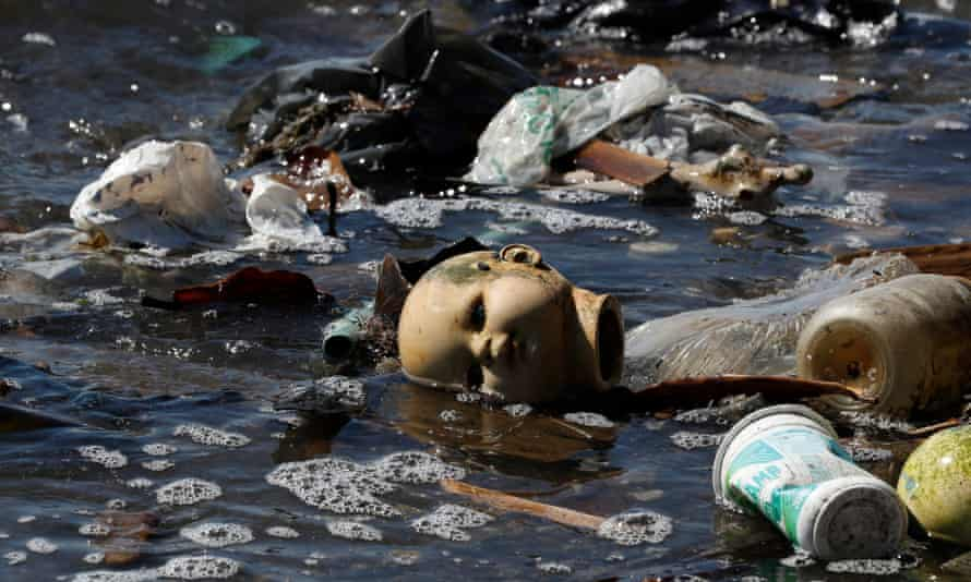 A doll's head and plastics among the rubbish and untreated sewage in the waters of Guanabara Bay