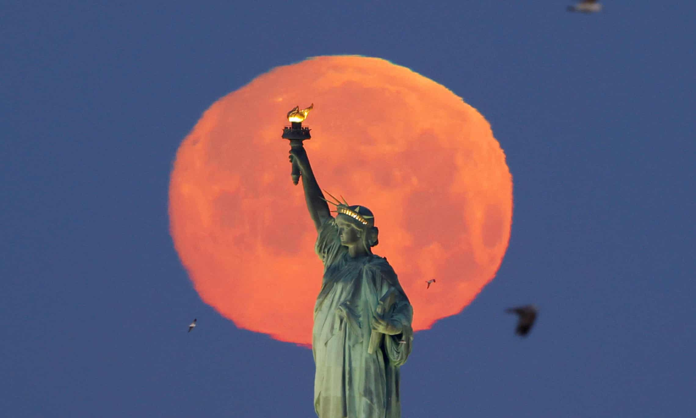 A pink supermoon sets behind the Statue of Liberty in New York City, New York