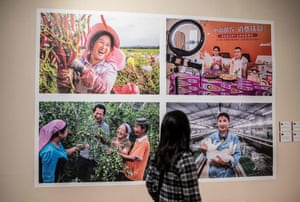 A woman views a photo exhibition featuring images taken in China's northwestern Xinjiang region.