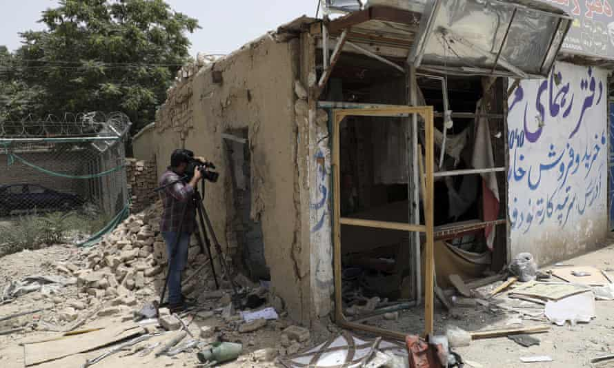 An Afghan journalist films the site of a bomb explosion in Kabul on 10 July