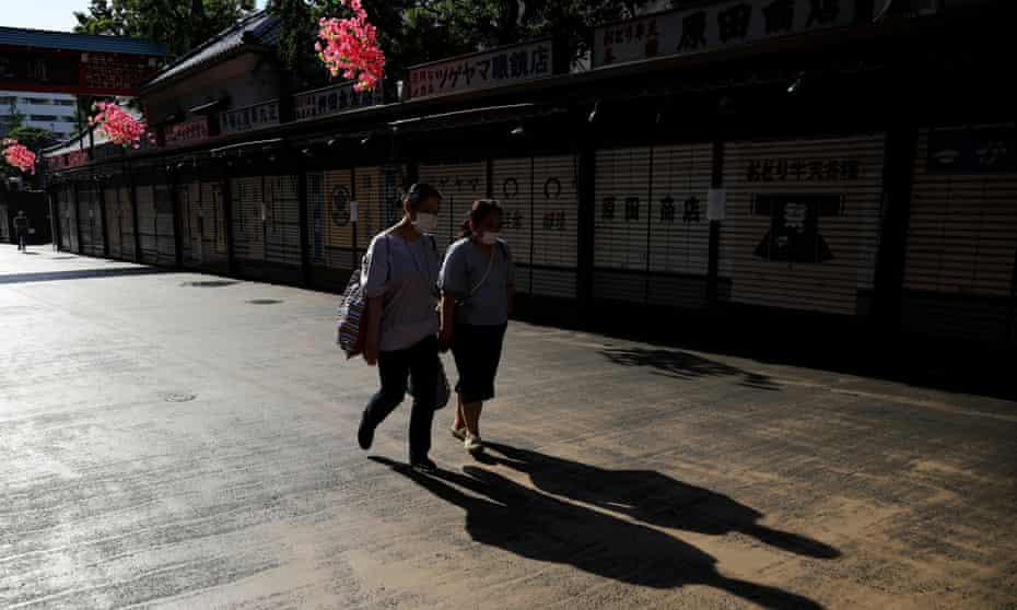 Women wearing protective masks walk past closed shops near the Sensoji temple in Tokyo