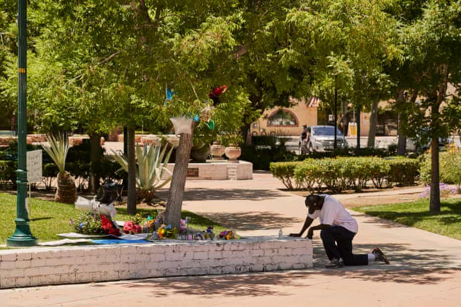 A man kneels near the tree where the body of Robert Fuller was found hanging, in Palmdale, California.