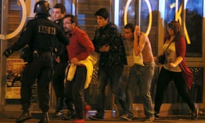French special forces evacuate people, including an injured man holding his head near the Bataclan concert hall in Paris, France.